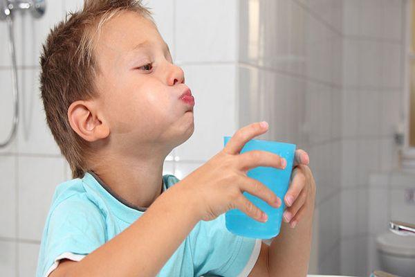 ребенок полоскает горло