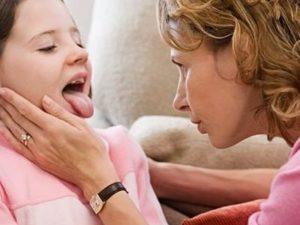 врач осматривает горло у девочки