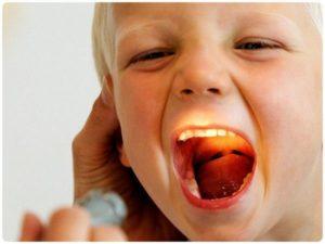 у мальчика проводят осмотр горла